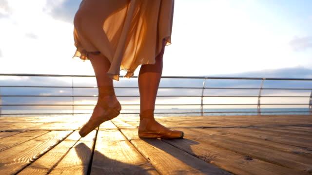 nahaufnahme von eine ballett-tänzerin füße, wie sie in pointe-übungen auf dem damm in der nähe von meer oder ozean, sonnenaufgang hintergrund, silhouette der frau die füße in spitzenschuhen praktiziert. ballerina zeigt klassisches ballett pas. slow-motion - ballettschuh stock-videos und b-roll-filmmaterial