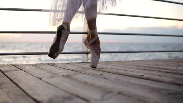 nahaufnahme einer ballett-tänzerin füße, wie sie punkt übungen praktiziert. ballerina geht elegant durch den damm in weißen pointe. slow-motion - ballettschuh stock-videos und b-roll-filmmaterial