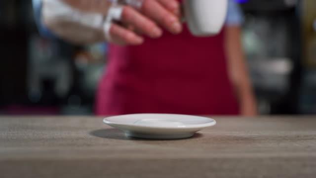 コーヒーカップをソーサーに置きながらコーヒーを作ったばかりのバーマンをクローズアップ。 - バーカウンター点の映像素材/bロール
