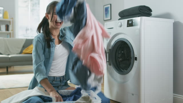 close up of a beautiful and happy brunette young woman sitting next to the washing machine in homely jeans clothes. she laughts and throws laundry clothes into the air. bright and spacious living room with modern interior. - stay at home parent stock videos & royalty-free footage