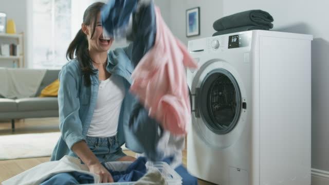 家庭的なジーンズ服の洗濯機の横に座っている美しい、幸せなブルネット若い女性のクローズ アップ。彼女の大笑いと空気中にスロー洗濯物。明るく広々 としたリビング ルームとモダンな� - 楽しい 洗濯点の映像素材/bロール