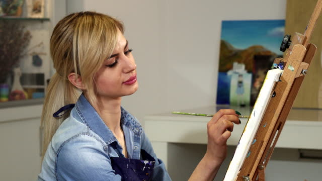 Close up of a beautiful female artist smiling painting artwork at her studio video
