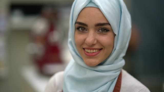 close up of a beautiful muslim business owner of a restaurant looking at camera smiling - origini video stock e b–roll