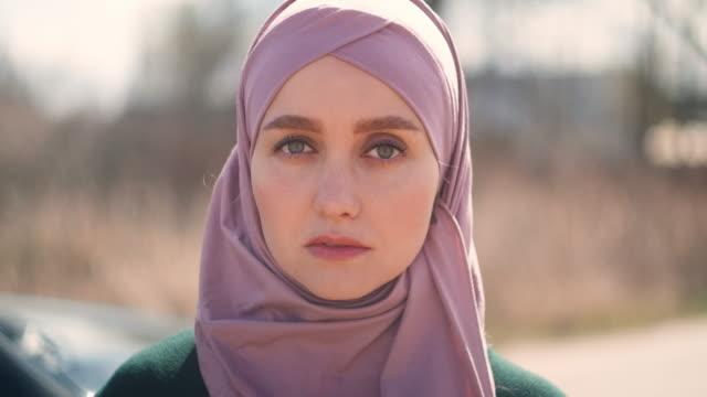 närbild av en vacker muslimsk kvinna tittar på kameran leende. porträtt av professionell ung muslimsk kvinna tittar på kameran leende glad bär traditionell huvudduk - anständig klädsel bildbanksvideor och videomaterial från bakom kulisserna