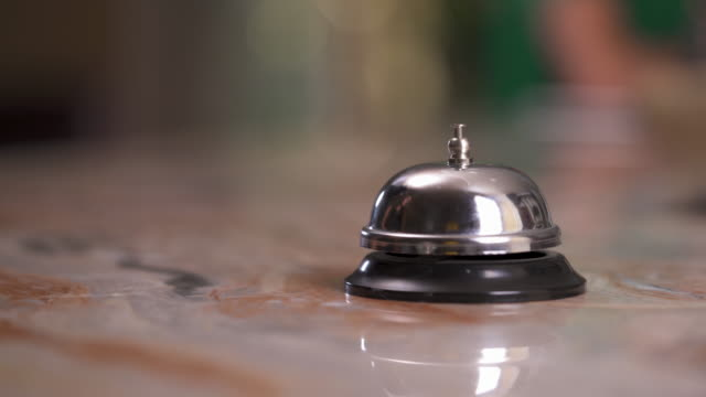 a close up of a bell at the reception desk at the blurred background. woman's hand moves ahead and presses the button - hotel checkin video stock e b–roll