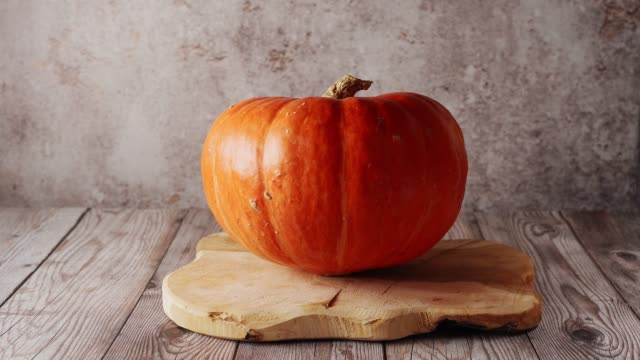 close up of a big orange pumpkin on wooden board and rustic background - pumpkin pie стоковые видео и кадры b-roll