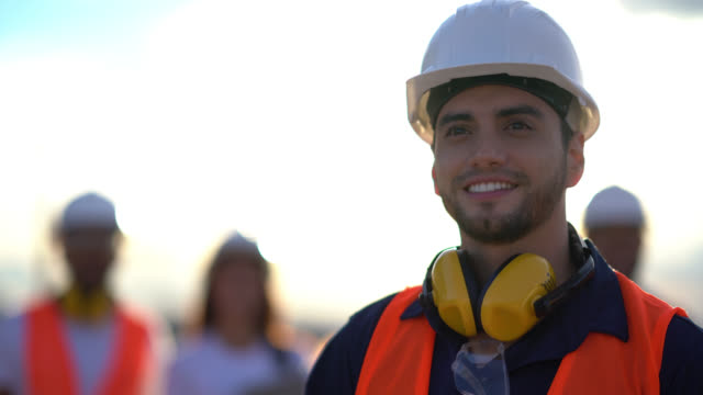 Close up of a blue collar worker looking away daydreaming very happy Close up of a blue collar worker looking away daydreaming very happy while wearing a safety helmet, protective googles and ear protectors work helmet stock videos & royalty-free footage