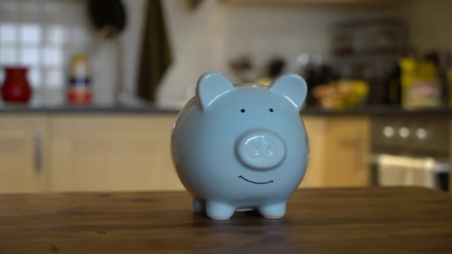 Close up of a blue piggy bank on wooden table