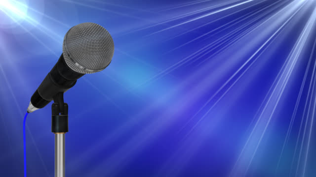Close up of a cardioid dynamic ball head microphone on a stand turning against a blue background with light flares video