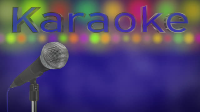 Close up of a cardioid dynamic ball head microphone turning on a stand the word karaoke is displayed in chrome 3D letters with a blue inlay there are also rows of colours representing lights and haze all on a blue background. video