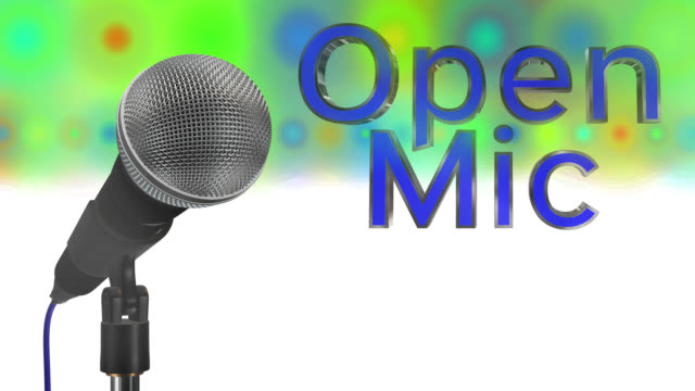 Close up of a cardioid dynamic ball head microphone turning on a stand the words open mic are displayed in chrome 3D letters with a blue inlay there are also rows of colours representing lights and haze all on a blue background saved with alpha channel video