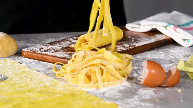 Close up of a cook using gloves gutting a pasta roll into tagliatelle noodles, then unrolling and adding them to a pile. Home cooking and pasta concept.