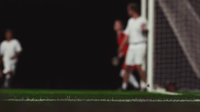 nahaufnahme eines corner kick und als kopfball in das tor zu einem fußballspiel bei nacht - geköpft stock-videos und b-roll-filmmaterial