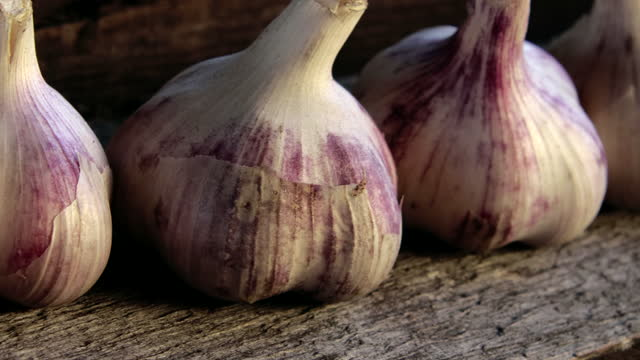 Close - up of a crop of garlic heads on a wooden background. Taken using a slider