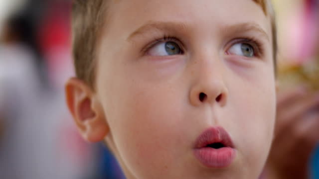 close up of a cute young boy puffing up his cheeks like he is blowing in slowmo - scolaro video stock e b–roll