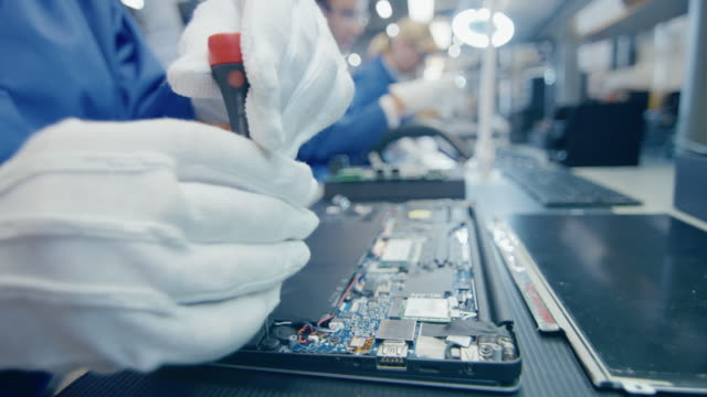 Close Up of a Female Electronics Factory Worker in Blue Work Coat Assembling Laptop's Motherboard with a Screwdriver. High Tech Factory Facility with Multiple Employees.