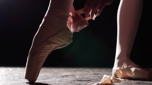 close up of a female hands tying pointe shoes on the leg isolated in spotlight on black background. - tutù video stock e b–roll