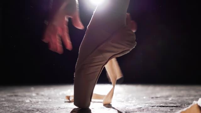 nahaufnahme einer frau hände binden spitzenschuhe am bein im rampenlicht auf schwarzem hintergrund isoliert. - ballettröckchen stock-videos und b-roll-filmmaterial