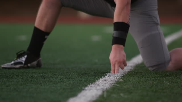Close up of a football player kicking the ball toward the goal posts Close up of a football player kicking the ball toward the goal posts kicking stock videos & royalty-free footage