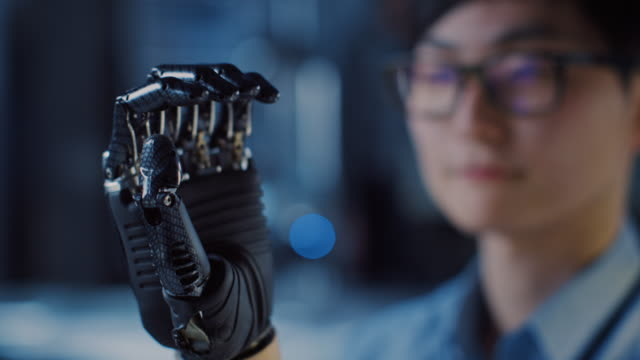 close up of a futuristic prosthetic robot arm being tested by a professional development engineer in a high tech research laboratory with modern computer equipment. - apparecchiatura medica video stock e b–roll
