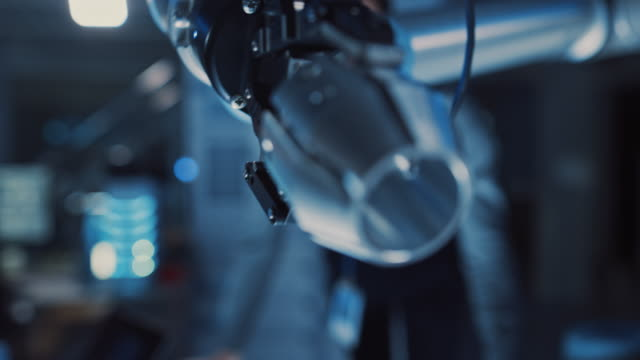 Video Close Up of a Futuristic Robotic Arm Moving a Metal Object and Placing It. Team of Engineers Observe This Advanced Process. They are in a High Tech Research Laboratory with Modern Equipment.