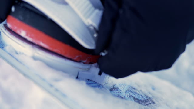 Close up of a girl fastening snowboard boots. Mounting bindings