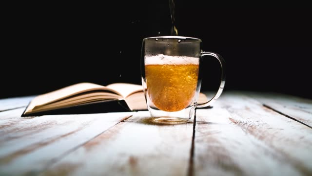 Close up of a glass cup being filled with golden tea with an open book behind on a wooden table. Relaxation and lifestyle concept.