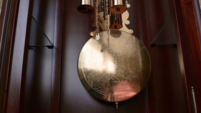close up of a grandfather clock pendulum moving - jeden przedmiot filmów i materiałów b-roll