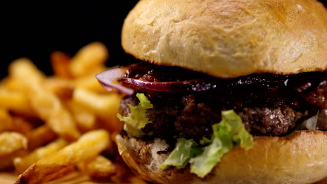 Close up of a grilled BBQ Burger with bacon and French Fries video