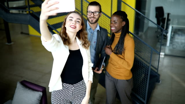 close up of a group of coworkers taking selfie - generazione y video stock e b–roll