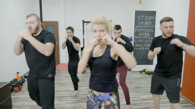 Close up of a group of male and female friends warming up together using boxing moves and punching without gloves video