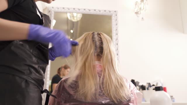 eine nahaufnahme von friseurmeisterin stehen auf der linken seite der blondine und einnahme von gefärbten stränge eins nach dem anderen. die ansicht von unten. - haartönung stock-videos und b-roll-filmmaterial