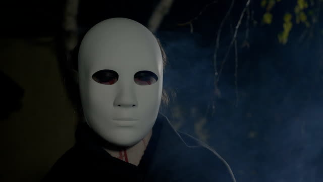 Close up of a halloween zombie with a white mask on his face looking straight to camera video
