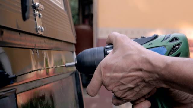 stockvideo's en b-roll-footage met sluit omhoog van een hand die een draadloze boor boor in de rug van een vrachtwagen houdt - elektrisch gereedschap