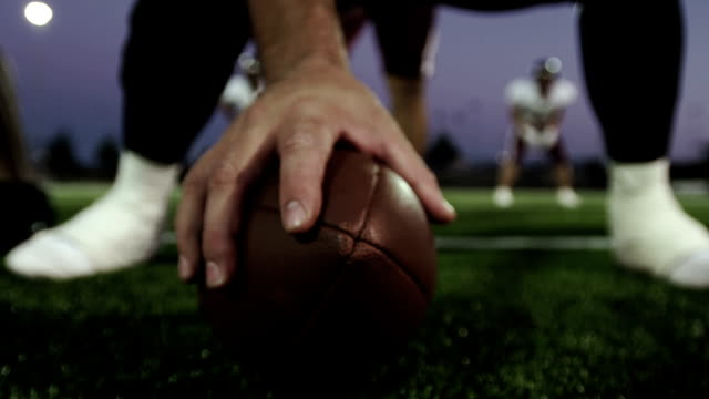 vídeos de stock e filmes b-roll de close up of a hand on a football about to hike it - bola