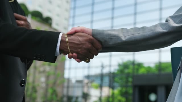 Close up of a handshake between an African American businessman and Japanese business woman outdoors Close up of a handshake between an African American businessman and Japanese business woman outdoors business handshake stock videos & royalty-free footage