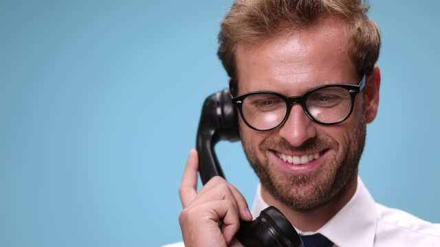 close up of a handsome businessman wearing eyeglasses, picking up a handset and talking on the retro telephone, laughing then hanging up on blue background close up of a handsome businessman wearing eyeglasses, picking up a handset and talking on the retro telephone, laughing then hanging up on blue background landline phone stock videos & royalty-free footage