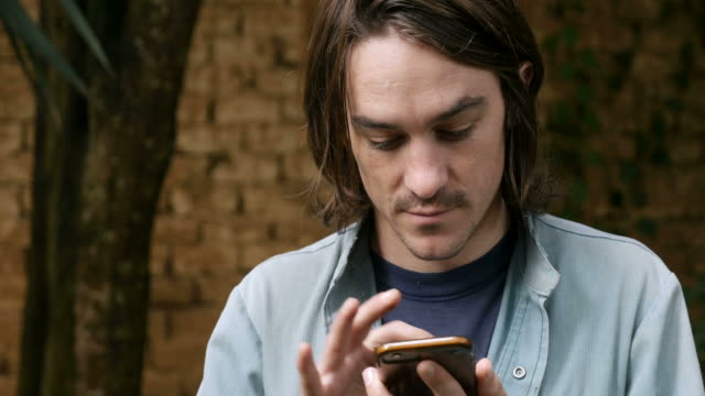 Close up of a handsome young man in 20s or 30s using smart phone video