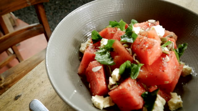 Close up of a healthy watermelon salad with mint and feta cheese in a bowl Close up of a healthy watermelon salad with mint and feta cheese in a bowl on a wooden table watermelon stock videos & royalty-free footage