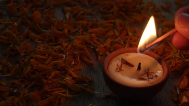 Close up of a Human lighting a Diya or a tradition lamp used for various Hindu festive celebrations for the festival of light- Diwali and also for others like Dussehra or prayers at home or a temple video