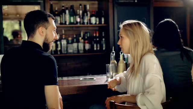 Close up of a loving couple having date in the restaurant. Young man and beautiful woman talking to each other sitting at bar counter. Girl is flirting with her friend laughing and smiling video