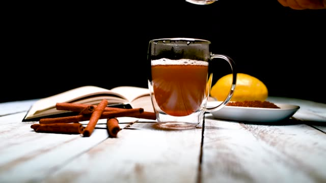 Close up of a male hand adding brown sugar to a cup of tea surrounded by cinnamon sticks, an open book and a lemon on a wooden table. Relaxation and lifestyle concept.