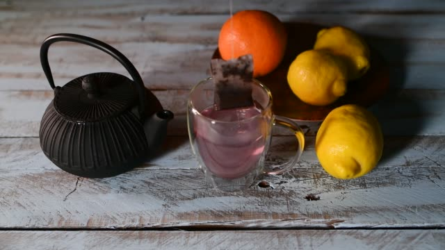 Close up of a male hand dipping a tea bag in and out of a cup with water surrounded by a teapot and fruits on a wooden table. Relaxation and lifestyle concept.
