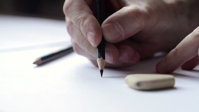 Close up of a male hand drawing with a black pencil video
