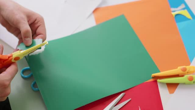 nahaufnahme eines männlichen hände, während er mit einer schere ein objekt aus dem farbigen papier schneidet - menschliche tätigkeit stock-videos und b-roll-filmmaterial