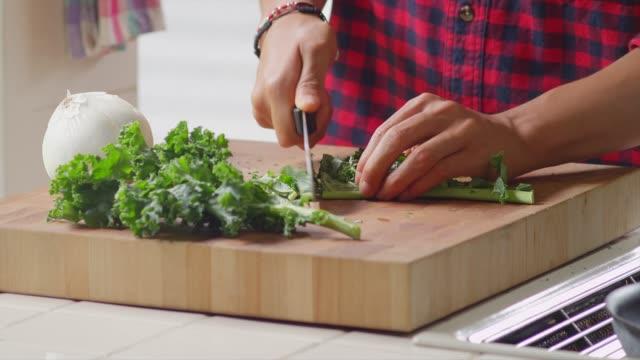 nahaufnahme eines mannes hacken gemüse in der küche - grünkohl stock-videos und b-roll-filmmaterial