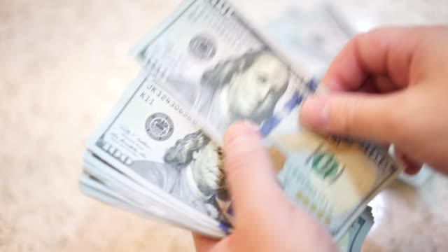 Close up of a man counting $100 bills video