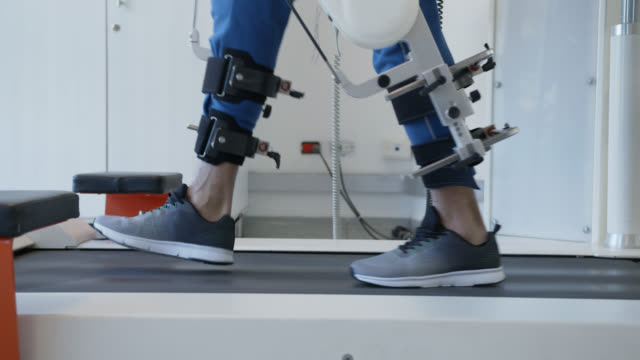Close up of a man doing physiotherapy with help of an exoskeleton robot at the hospital video