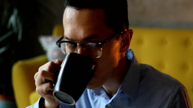 コーヒーを飲んで彼のラップトップで働く男のクローズアップ - クレジット決済点の映像素材/bロール