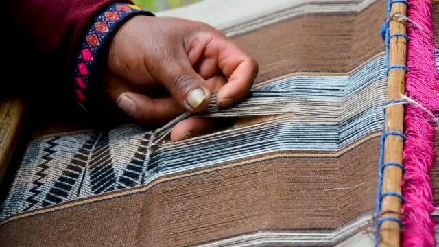 vídeos de stock e filmes b-roll de close up of a man hands weaving on a loom as his ancestors used to do - américa do sul